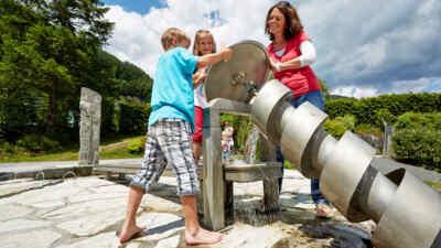 Kinder mit Frau versuchen sich an der Archimedesschraube